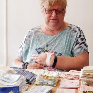 Jeanne sorteert stofjes bij de dagbesteding